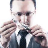 電子タバコにリキッドを補充するビジネスマン